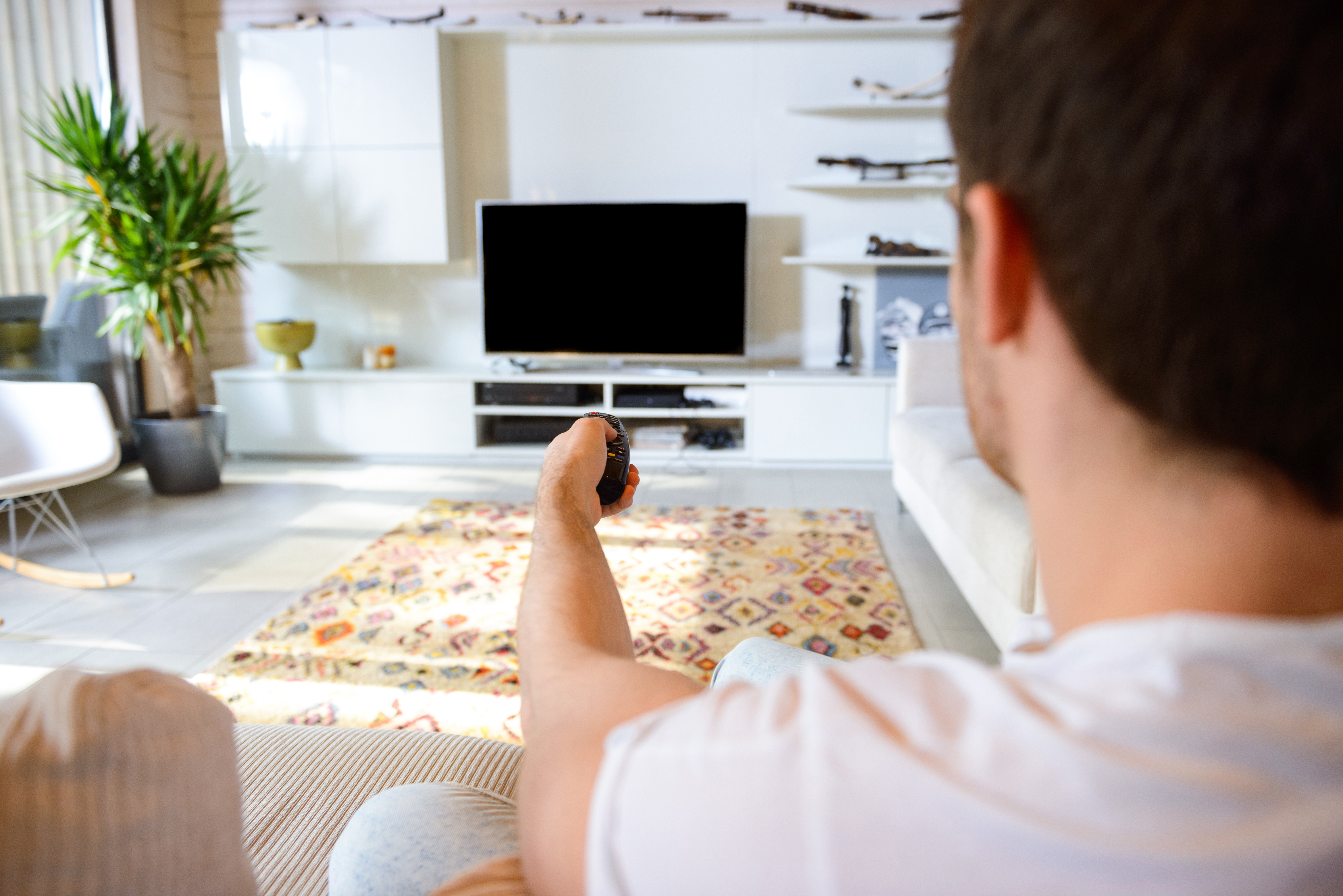 man-sitting-against-tv-PYS8SNJ